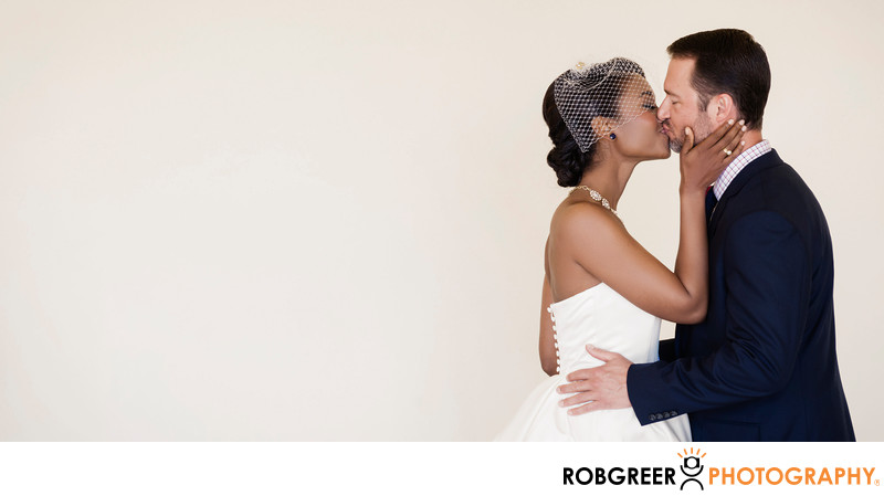 Bride and Groom Kissing Happily Against Blank Wall