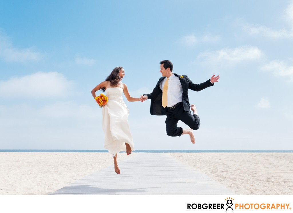 Couple Jumps: Beach Boardwalk Wedding